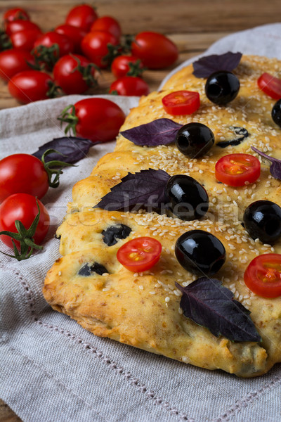 Italian bread focaccia with olive, basil and cherry tomato Stock photo © TasiPas