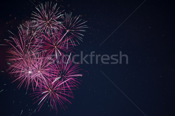 Maroon red pink celebration fireworks over night sky Stock photo © TasiPas