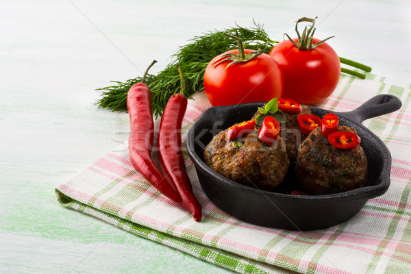 Grilled meatballs served with chili pepper slices in cast iron s Stock photo © TasiPas
