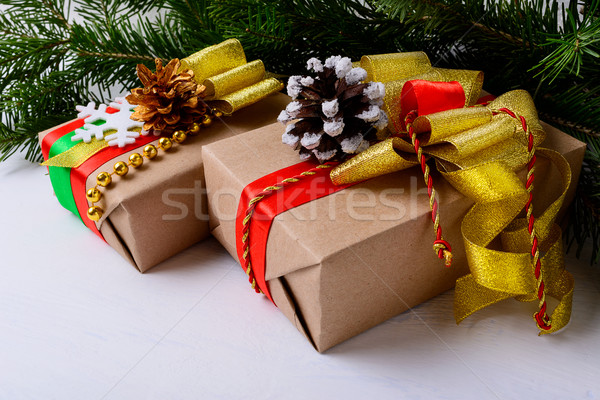 Christmas presents decorated with snowy and golden pine cones Stock photo © TasiPas