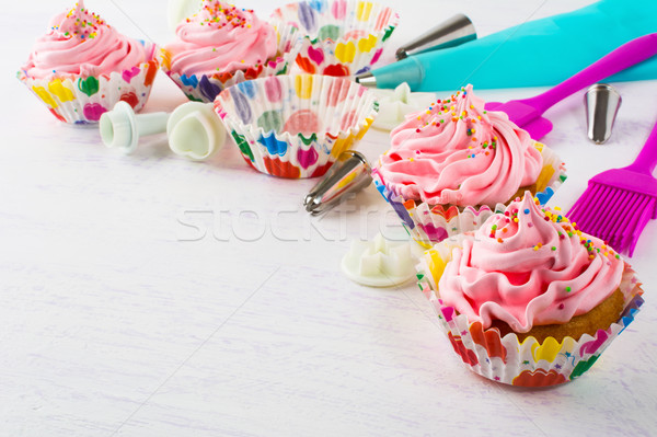 Pink birthday cupcakes  and cookware background Stock photo © TasiPas