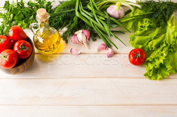 Tomato, olive oil, and garlic on white wooden background Stock photo © TasiPas