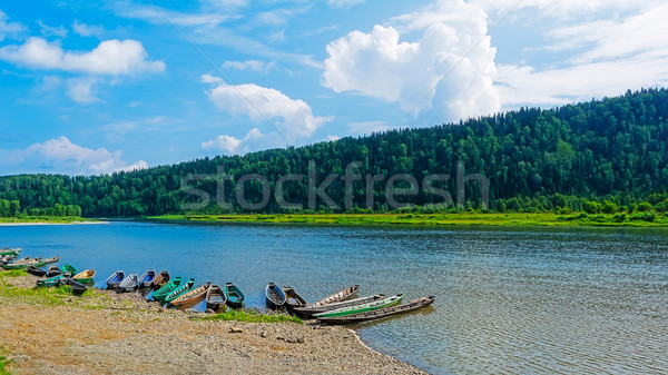 Beautiful river landscape with boats moored to the bank of the r Stock photo © TasiPas