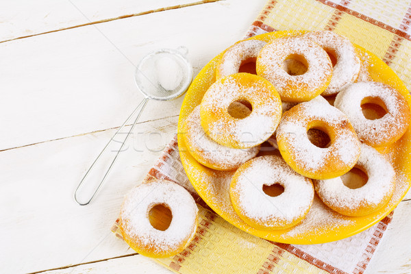 Donuts with caster sugar served on yellow plate top view copy sp Stock photo © TasiPas