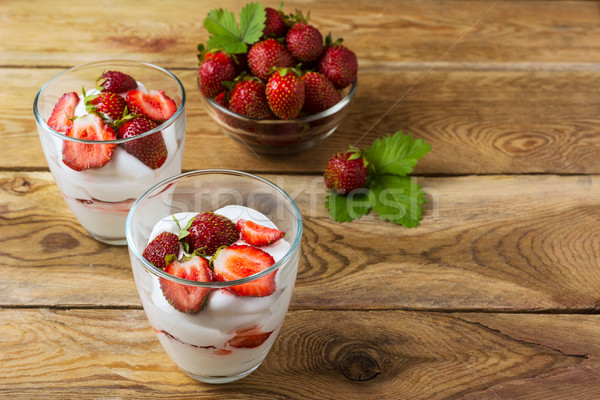 Summer layered cream dessert and ripe strawberry in glass bowl Stock photo © TasiPas
