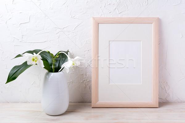 Wooden frame mockup with tender white lily in vase Stock photo © TasiPas