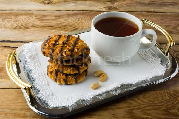 Chocolate glacê bolinhos amendoins copo chá Foto stock © TasiPas