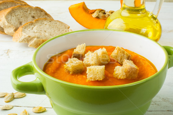 Creamy pumpkin soup with croutons in a green bowl  Stock photo © TasiPas
