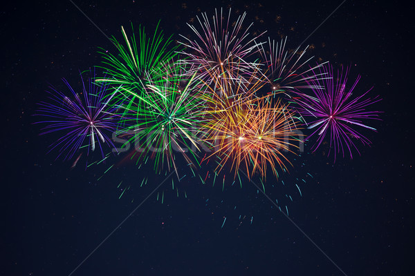 Blue green purple orange fireworks over starry sky Stock photo © TasiPas