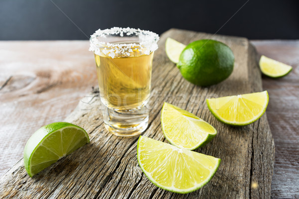 Tequila shot with lime on rustic wooden background Stock photo © TasiPas