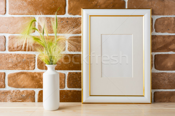 Gold decorated frame mockup with ornamental grass exposed brick  Stock photo © TasiPas