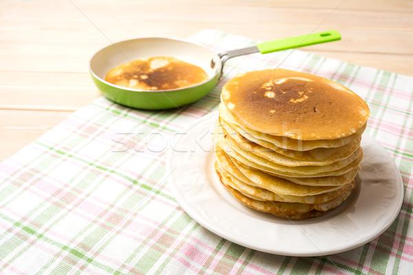 Stack of homemade breakfast pancakes and green pan Stock photo © TasiPas