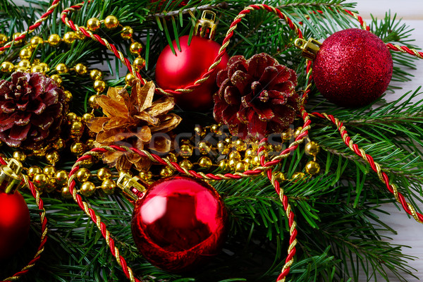 Golden Christmas beads, fir branches and red ornaments Stock photo © TasiPas
