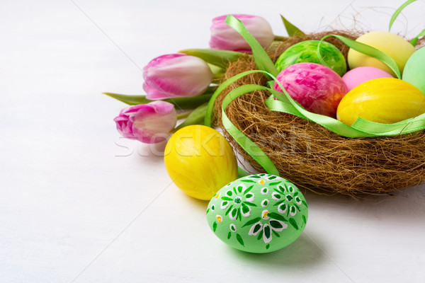 Easter painted eggs in nest and pink tulips, copy space. Stock photo © TasiPas
