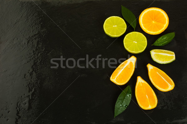 Limes and lemons on black background, copy space Stock photo © TasiPas