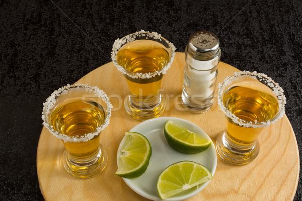 Três ouro tequila cal sal preto Foto stock © TasiPas