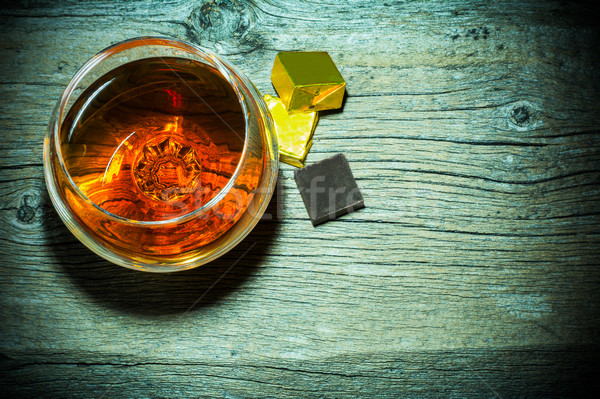 Bourbon snifter and chocolate on old wooden background top view Stock photo © TasiPas