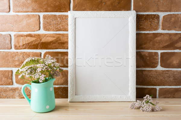 White frame mockup with creamy pink flowers near exposed bricks Stock photo © TasiPas
