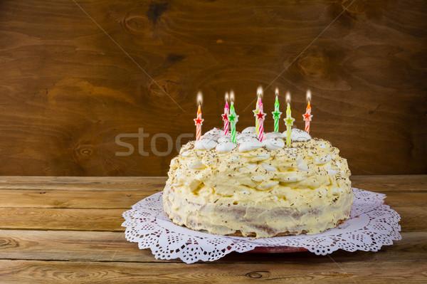 Birthday meringue cake with burning candles Stock photo © TasiPas