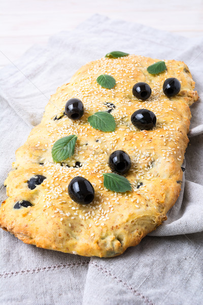Italian bread focaccia with olive, garlic and mint, vertical Stock photo © TasiPas