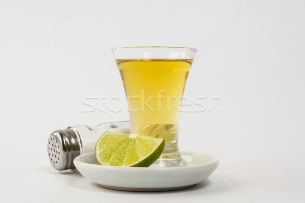 Gold tequila shot on the white background Stock photo © TasiPas