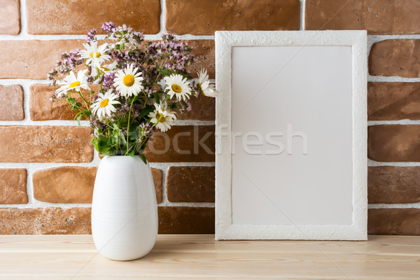 White frame mockup with wildflowers bouquet near exposed brick w Stock photo © TasiPas