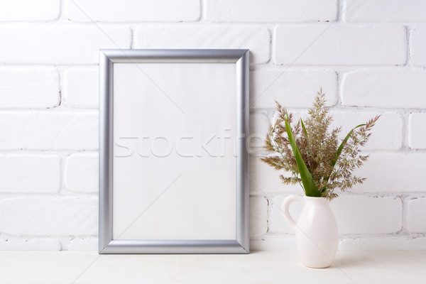 Silver frame mockup with grass and green leaves in pitcher vase  Stock photo © TasiPas