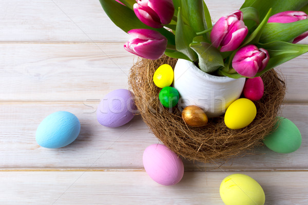 Easter table centerpiece with decorated eggs in nest and pink tu Stock photo © TasiPas