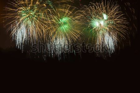 Golden green yellow fireworks located left side  Stock photo © TasiPas