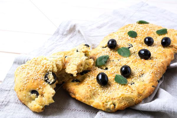 Italian bread focaccia with olive and herbs on linen napkin Stock photo © TasiPas