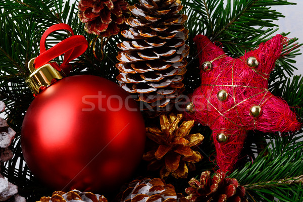 Christmas red ornaments and snowy decorated pinecone Stock photo © TasiPas