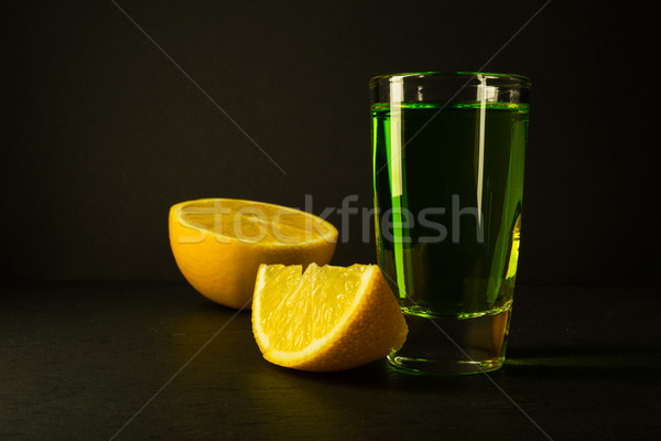 Absinthe and lime on black background Stock photo © TasiPas