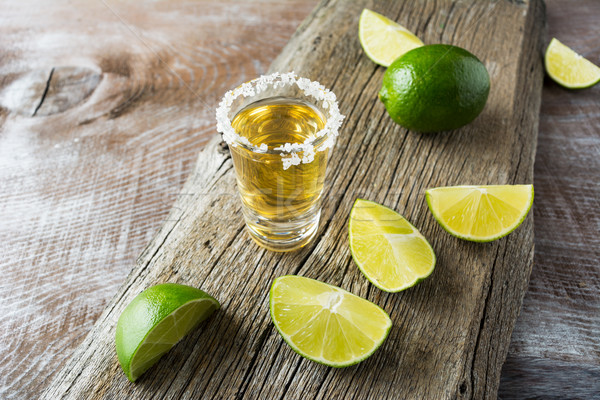 Tequila shot with lime slices on rustic wooden background Stock photo © TasiPas