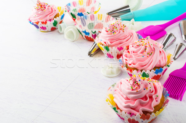 Decorated pink birthday cupcakes  and cookware Stock photo © TasiPas