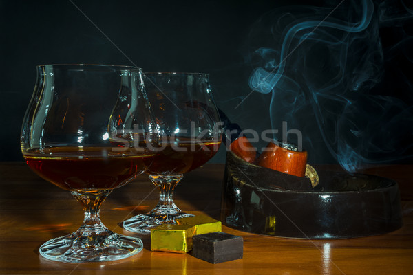 Scotch drink and tobacco pipe with smoke on black background Stock photo © TasiPas