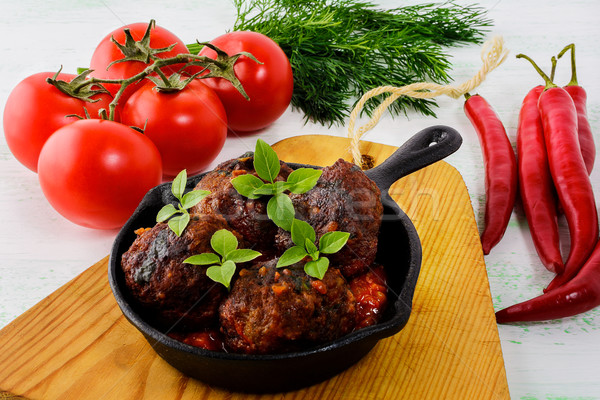 Meatballs with chili pepper and tomato served in cast iron skill Stock photo © TasiPas
