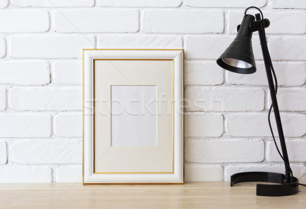 Gold decorated frame mockup with black lamp Stock photo © TasiPas