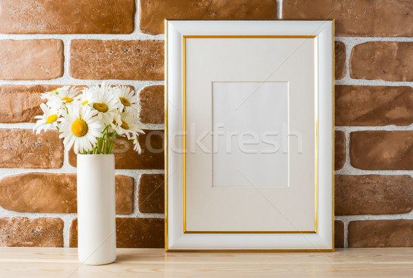 Gold decorated frame mockup with daisy bouquet exposed brick wal Stock photo © TasiPas