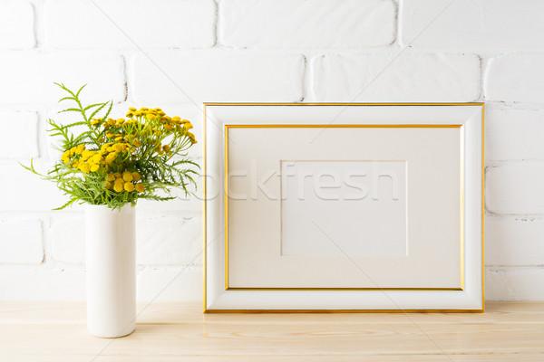 Gold decorated landscape frame mockup near painted brick walls Stock photo © TasiPas