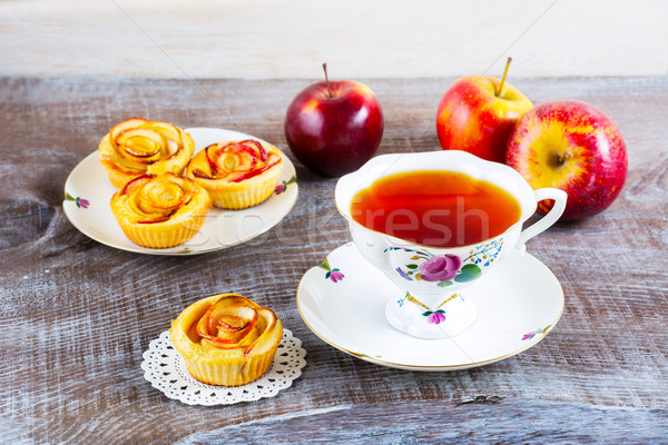 Cup of tea and small apple roses shaped pies Stock photo © TasiPas