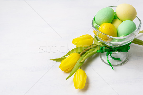 Easter green and yellow painted eggs in the vase and tulips, cop Stock photo © TasiPas
