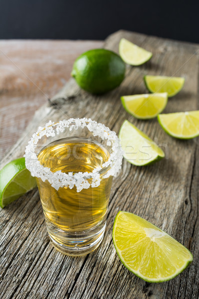 Gold tequila shot with lime slices on rustic wooden table Stock photo © TasiPas