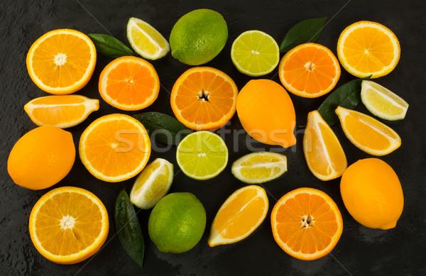 Lime, lemon, orange and tangerine on black background Stock photo © TasiPas