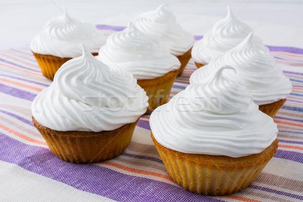 White cupcakes on the striped linen napkin Stock photo © TasiPas