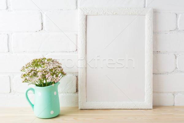 White frame mockup with soft pink flowers near exposed bricks Stock photo © TasiPas