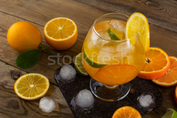 Tropical iced fruit cocktail on wooden table Stock photo © TasiPas