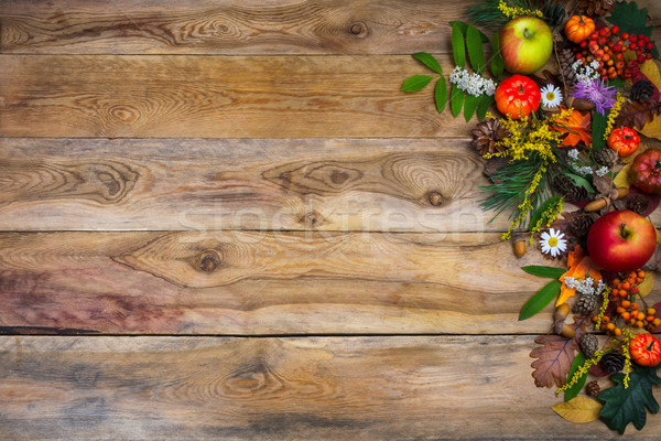 Fall background with pumpkin and green leaves on wooden table  Stock photo © TasiPas