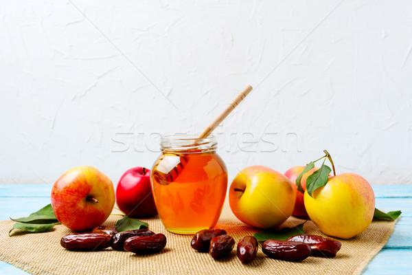 Honey jar, dates and ripe apples on burlap napkin Stock photo © TasiPas