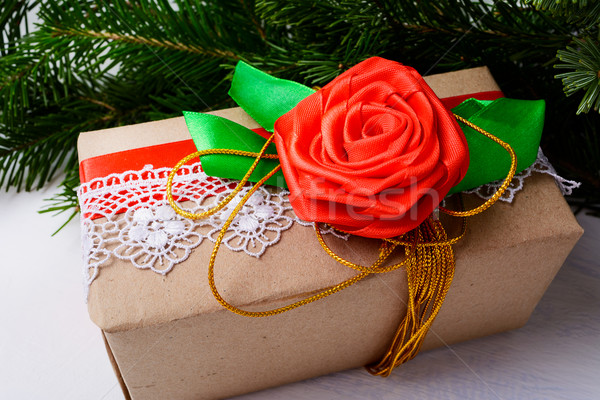 Christmas kraft paper wrapping present with golden ribbon and ro Stock photo © TasiPas