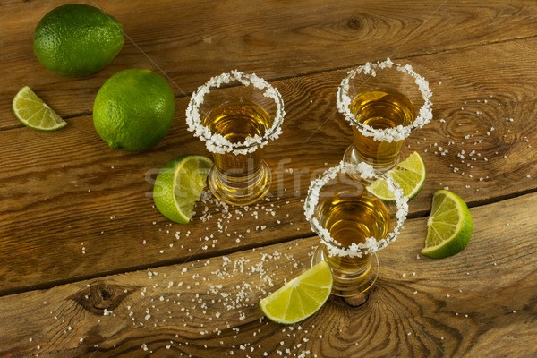 Tequila shots with lime and salt on the wooden background top vi Stock photo © TasiPas